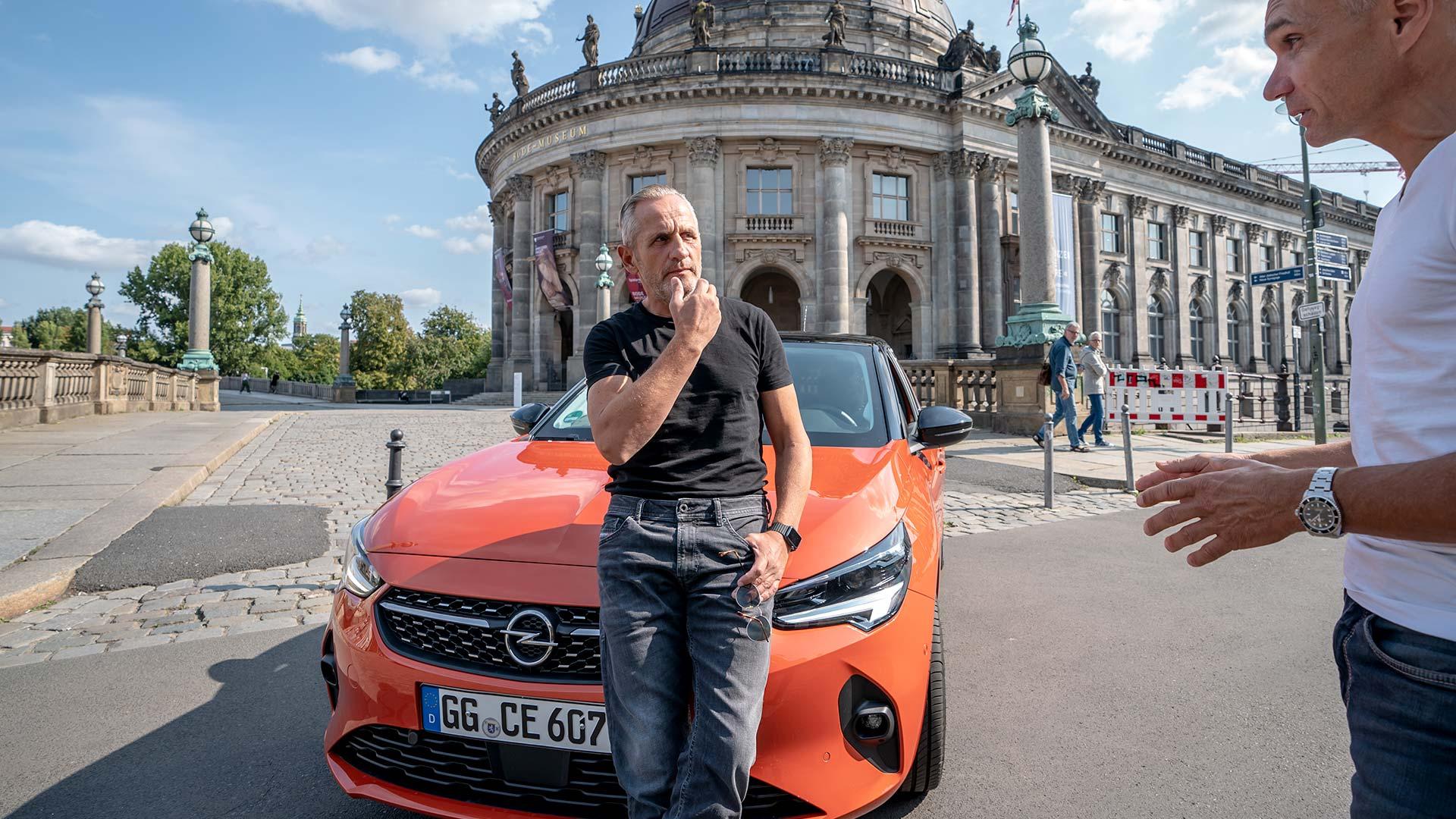Schauspieler Tim Wilde lehnt in Berlin an einem Opel Corsa-e.