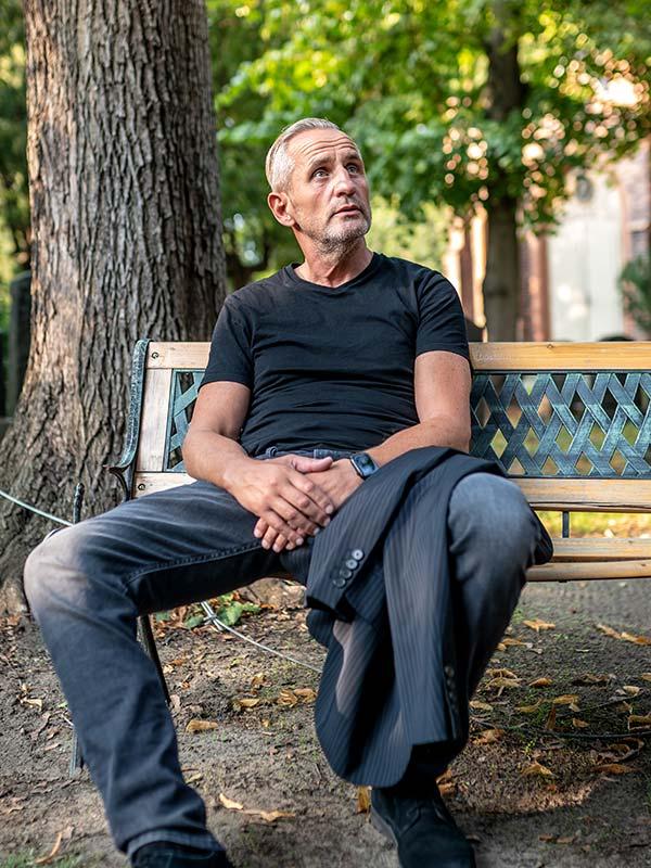 Schauspieler Tim Wilde sitzt auf einer Bank